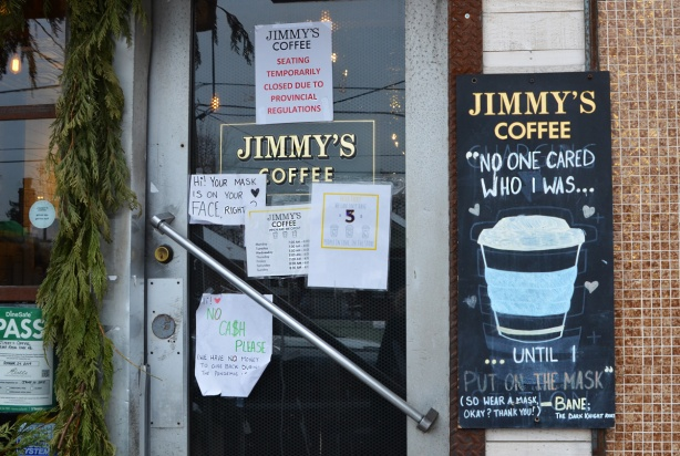 signs on the door of Jimmys coffee shop, wear a mask, wear it right, and other covid notices