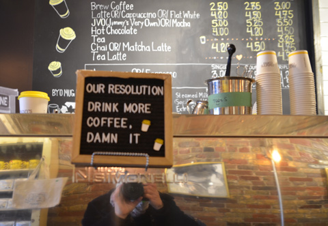inside Jimmys coffee, a sign on the bar that says our resolution drink more coffee damn it