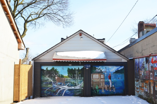 two garage doors side by side in an alley with murals painted on them, a deer with antlers on the left and a man fishing in a river on the right