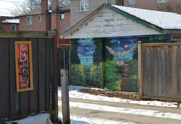 double car garage in an alley with murals painted on them, owl theme,