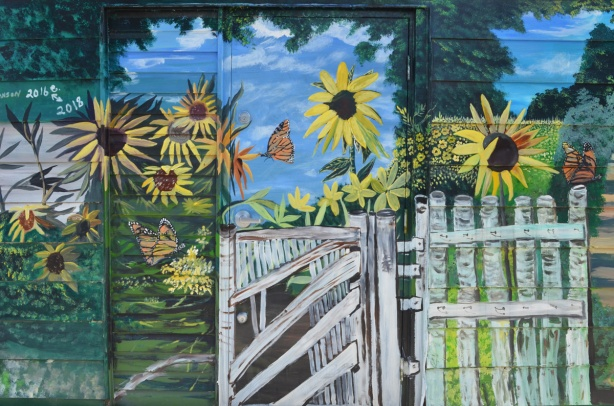sunflowers and butterflies on a summer day, and a gate made of birch branches, a mural in an alley by Bc johnson