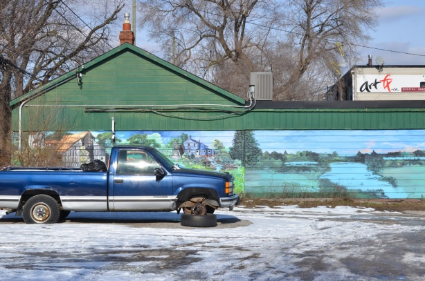a blue pickup truck with one tire missing, parked in a vacant lot, in front of a farmyard scene mural with fields and a pond