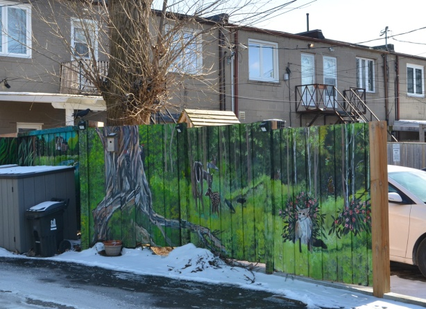 a woodlands theme mural on a wood fence between two properties in a lane, a tree trunk in the mural matches the large tree behind the fence