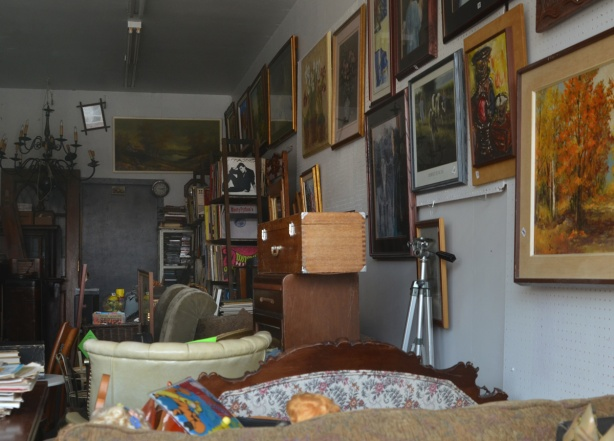 looking in the window of a junk vintage store, framed pictures on the wall, a shelf of old records, a trunk, and other stuff