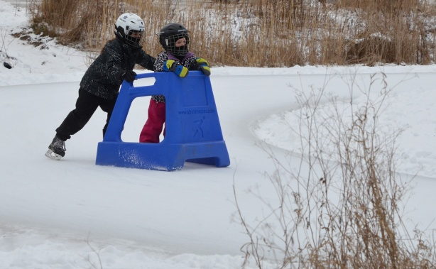 two kids skating, one is pushing the other who is holding onto a blue plastic support