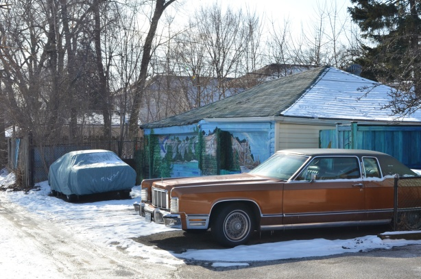 an old rust coloured Lincoln Town Car parked in an alley, garage doors behind it are covered in murals by bc johnson