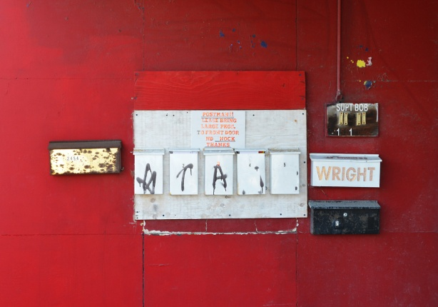 a red wall in front of a building, mailboxes on it, 8 mailboxes, also two buzzers under a sign that says Supt Bob
