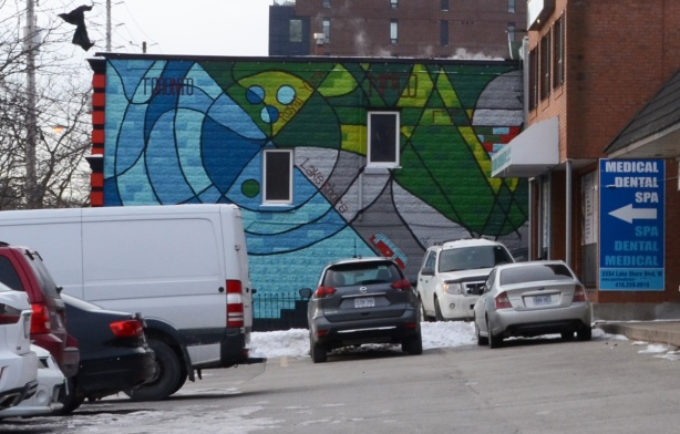 mural on the side of a building, cars parked in front of it