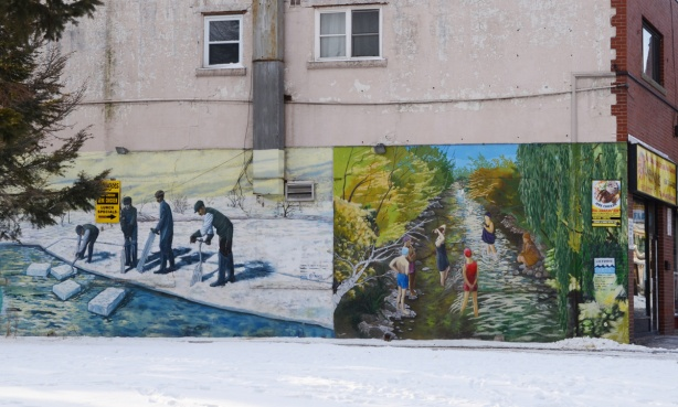 two historical murals on the side of a building, one is boys ice fishing and the other is people swimming in the creek