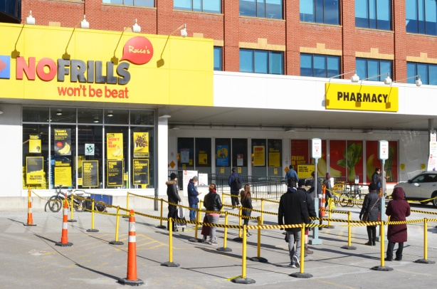 people lined up waiting to get into No Frill grocery store, keeping the 2 metres apart