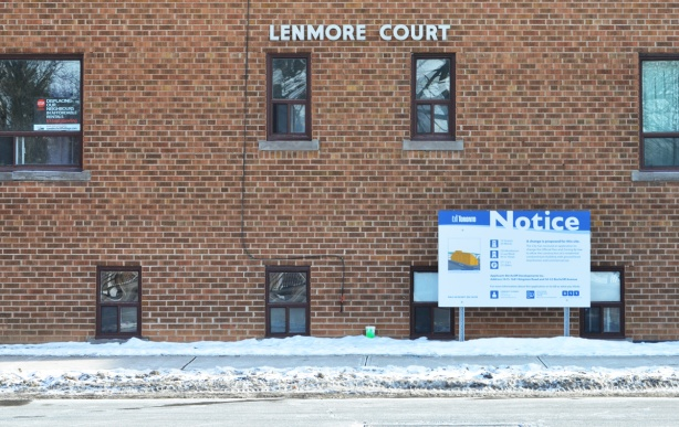 Lenmore Court, an older brick apartment complex, with a blue and white Toronto notice of development sign on it