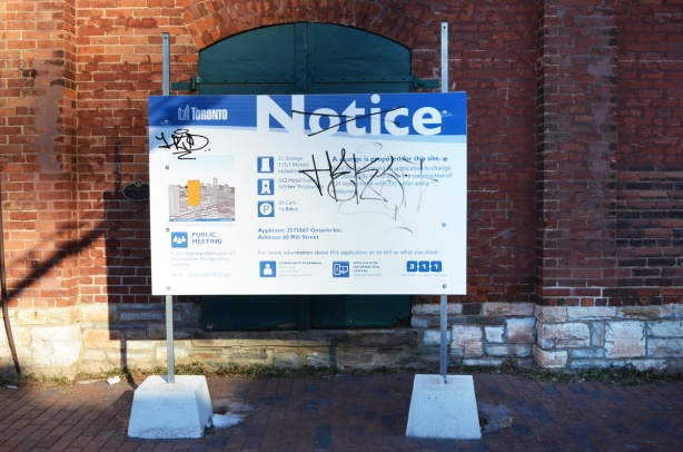 blue and white city of toronto development notice in front of old brick building in distillery district