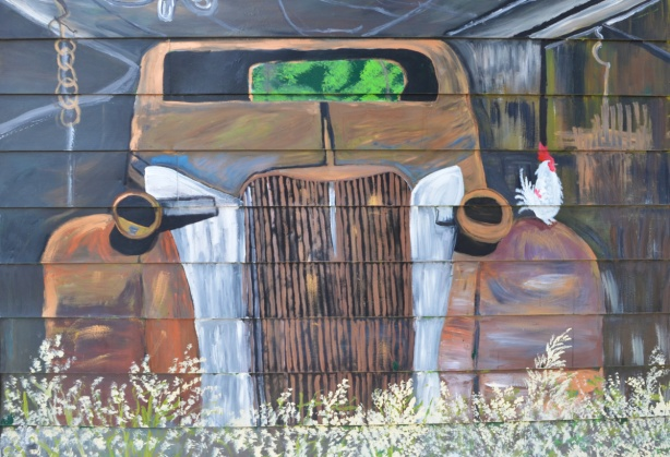 mural, front of an old rusty car with a white chicken standing on one fender