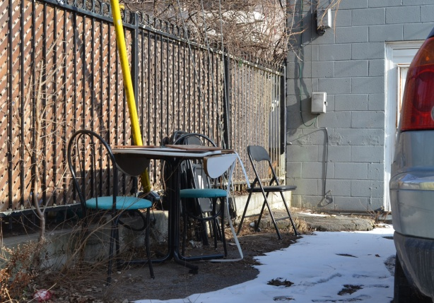 table and chairs behind a building in an alley