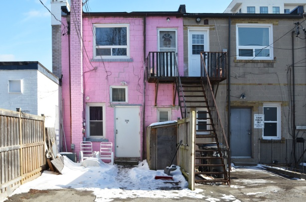 back of a store & apartment, in an alley, building is brick painted pink, stairs to upper level doors, snow on the ground