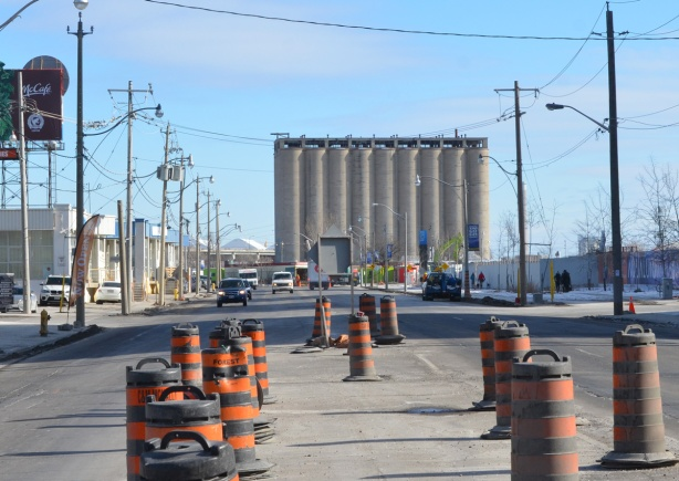 looking east on Queens Quay from Lower Sherbourne with old concrete silos in the distance, lots of orange and black traffic cones in the middle of the street in the foreground