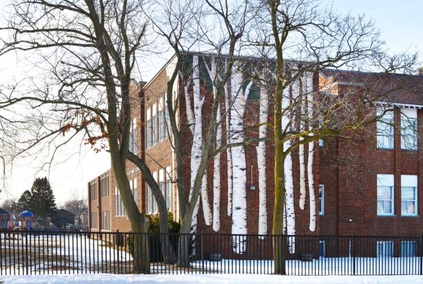 Birch cliff public school, a two storey red brick building, with a large mural of birch trees on one exterior wall