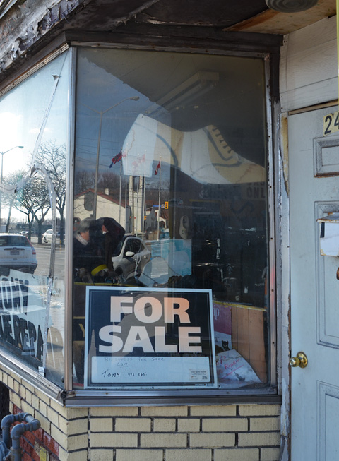 looking in the window of a shoe repair business with a for sale sign in the window