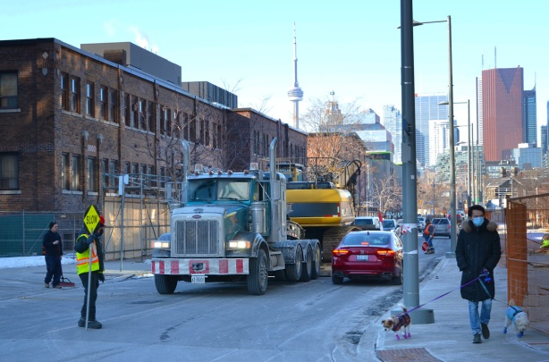 flat bed truck carrying machinery, and little red car on street, man holding slow stop sign by construction site , man on sidewalk walking two small dogs
