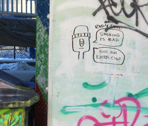 black marker scrawl graffiti on a concrete post, drawing of man's face and head with words about smoking