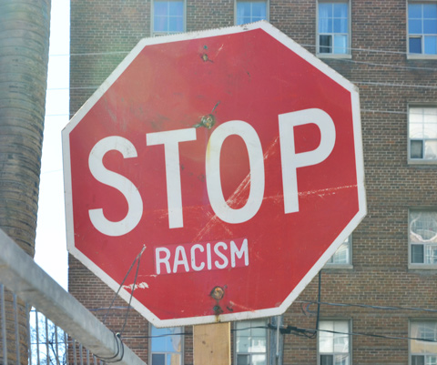 red octagonal stop sign that now says stop racism