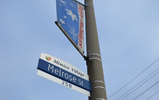 Toronto street sign for Mimico village, Melrose street,, on the same pole is a banner above it that says happy holidays