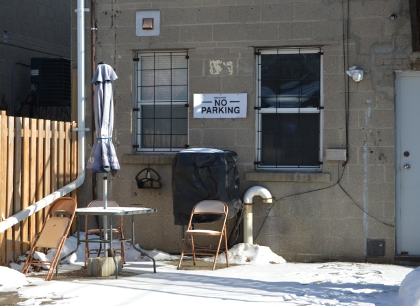 chairs and round table outside, in back of building, in an alley, also patio umbrella, folded up