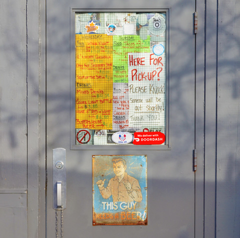posters and signs on the door of a bar