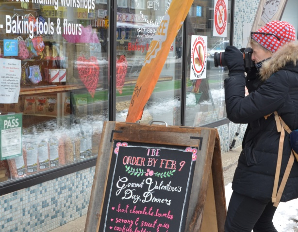 photographer taking a picture of a store window, masks, baking things, red hearts,