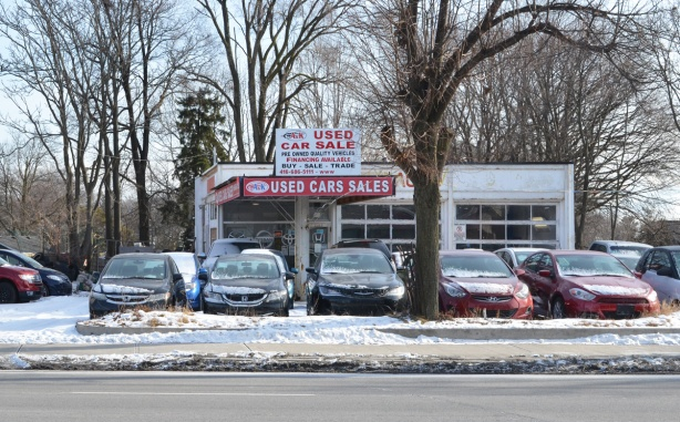 an old gas station that is now a used car dealership, with many cars parked outside in the snow