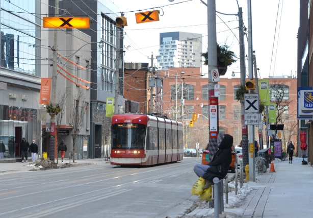 King street 504 TTC streetcar, person sitting onrailing and waiting for streetcar