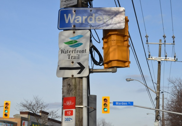 Warden street sign, with traffic signals, also a sign pointing south to the Waterfront Trail