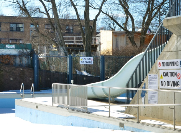 outdoor waterslide at an outdoor pool closed for the winter, sign that says no running, no diving