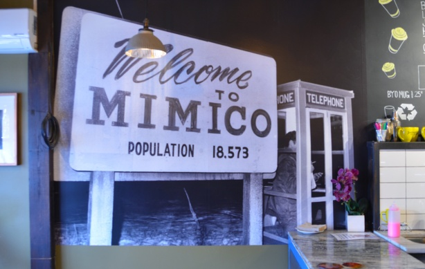 large photograph on a coffee shop wall of a welcome to mimico sign beside an old phone booth with someone inside it