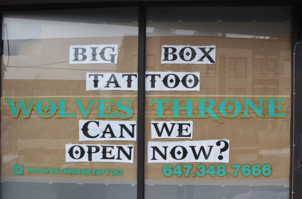 window of a tattoo shop, rattan blinds closed, painted on window is sign that says big box tattoo, wolves throne, can we open now?