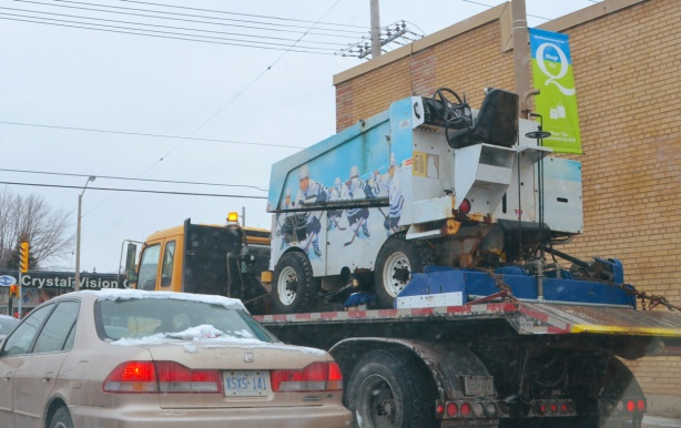 a zamboni on the back of a tow truck, travlling on a toronto street