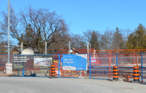 signs on construction fence at Agincourt GO station showing picture of new station
