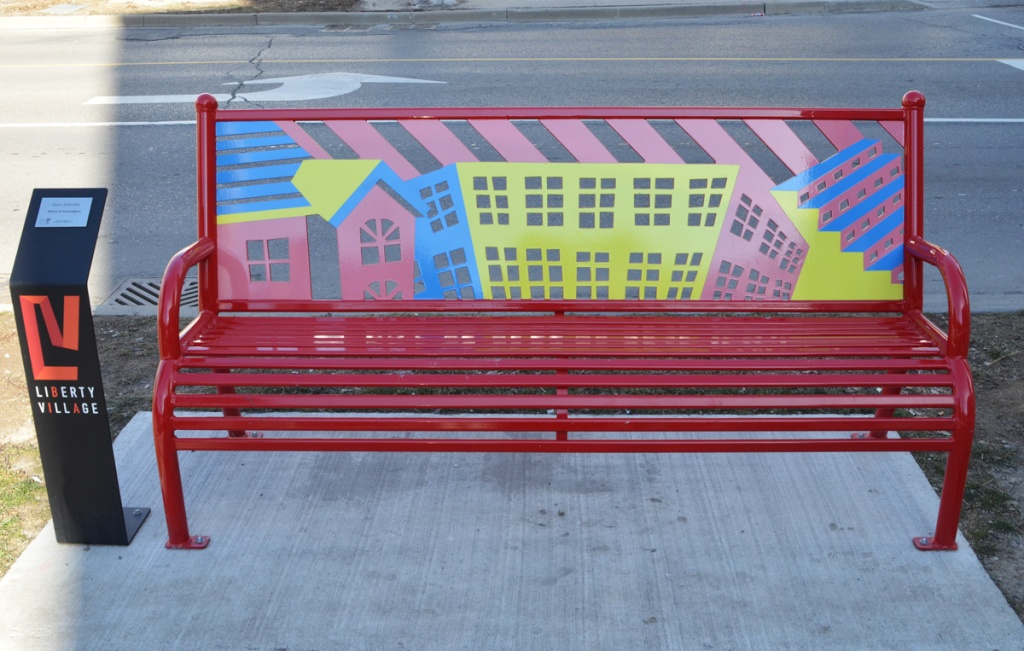 a bench in Liberty Village with the back piece decorated in houses in primary colours