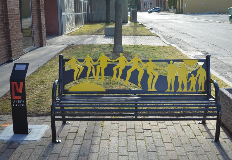 A black metal bench between the sidewalk and street, the back of the bench has yellow figures all holding hands