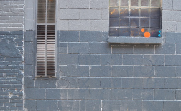 a grey wall with a window, some coloured circles painted on the window