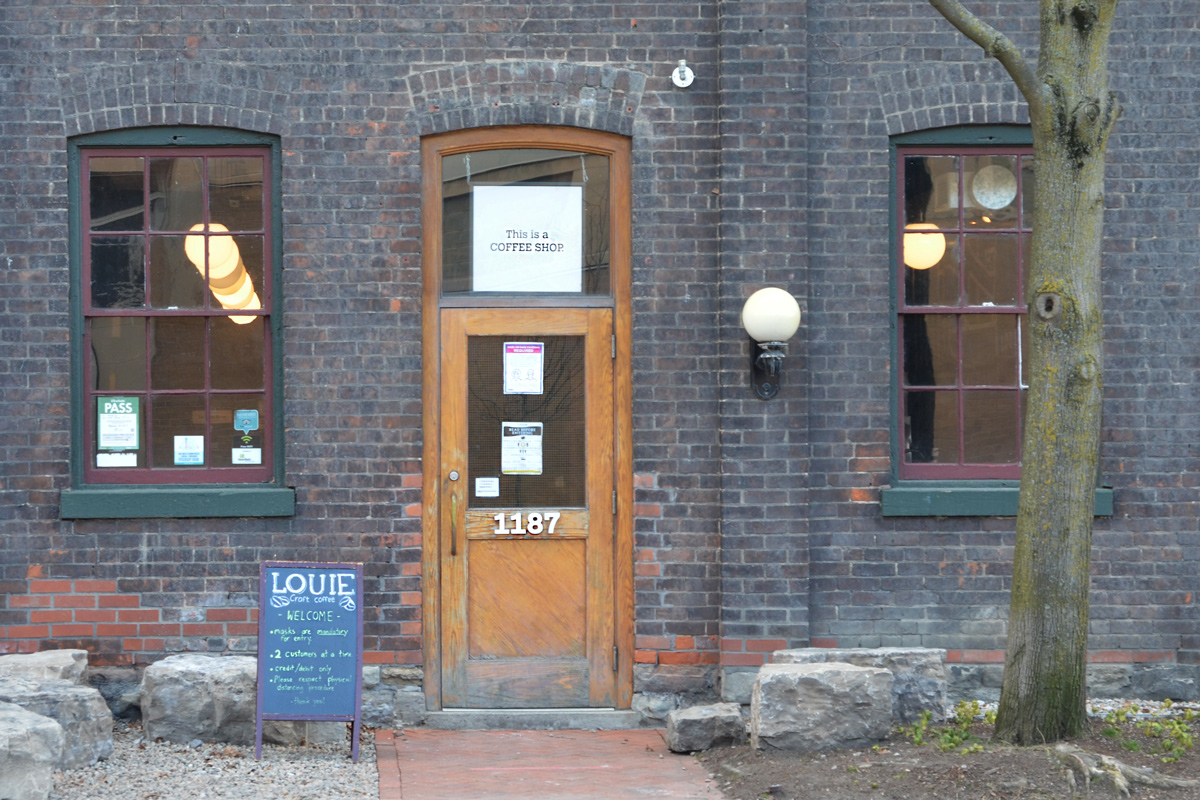 exterior of Coffee Shop Loiue with sign in window above door that says this is a coffee shop
