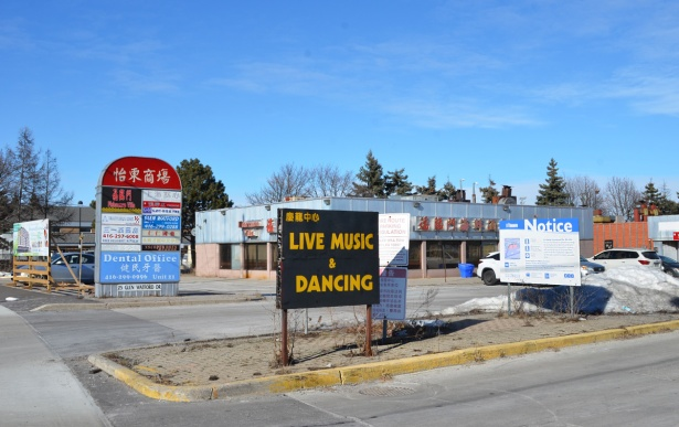 sign advertising live music and dancing in front of a strip mall that is about to be redeveloped