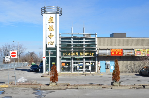 Dragon centre, Chinese market, now closed and empty, empty parking lot and two small dead cedar trees