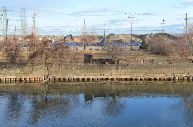 construction in the background, blue digger, vacant land, and the Keating channel in the foreground, ducks in the water