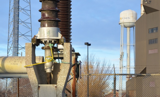 close up of part of electrical station equipment, with water tower in the background with word Ponds written on it