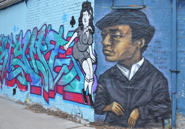 Huey Newton mural by elicser on the end of a wall, a mural beside it with a buxom woman in tight clothes