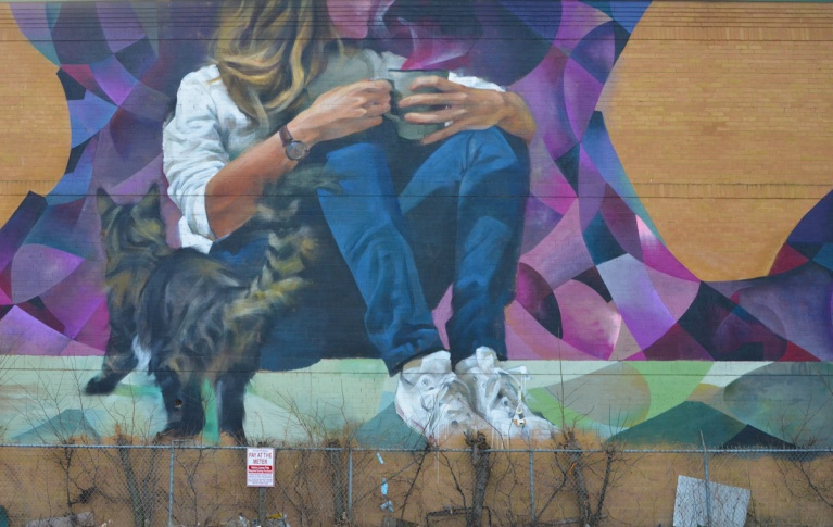 mural of a woman sitting drinking coffee except the top part of her head and face are missing