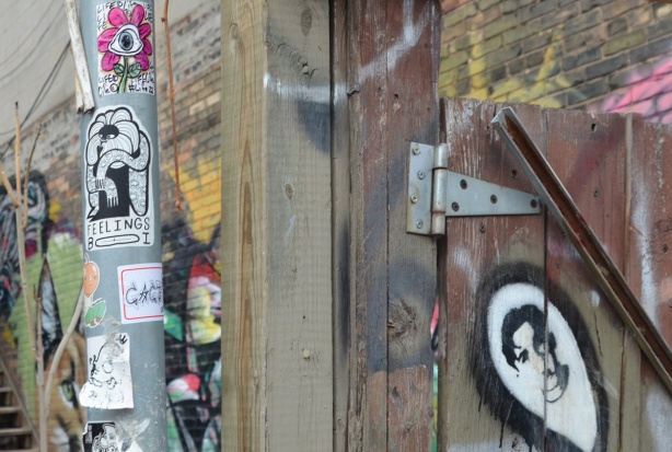 stickers on a pole, a daisy in pin, a feelings boi, beside a wood fence and gate with stencil graffiti of a man's face in a white oval framed in black