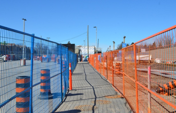 2 fences, one on either side of a pedestrian pathway through a construction area at Agincourt GO station
