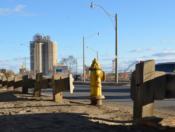 yellow fire hydrant in front, guard rails along the side of Lakeshore Blvd, with Lafarge silos in the background
